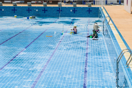 A group of technicians are repairing the damaged pool. Stockfoto