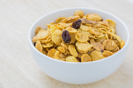 Mix corn flake cereal in a white bowl on the table. photo