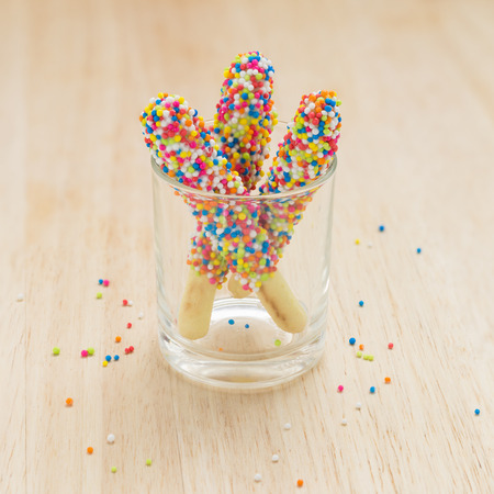 Sweet bread sticks with chocolate and colorful sugar sprinkles. photo