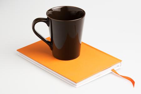 naranja: Naranja cuaderno pluma blanca y una taza de caf� sobre fondo blanco Foto de archivo