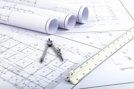 Boussoles et règle-échelle d'architecte placés sur le bureau, rempli de plans de construction. Afin de travailler dans un bâtiment Banque d'images