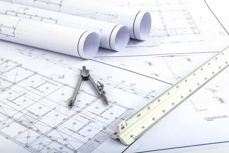 architect plans: Compasses and Architect scale ruler placed on the desk, filled with building plans. In order to work in a building Stock Photo