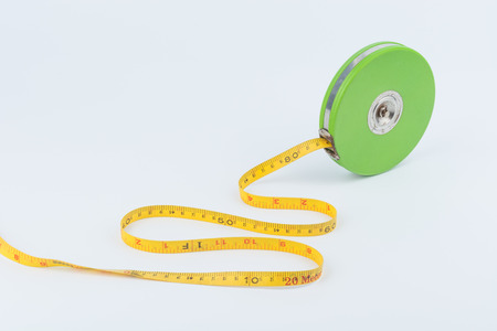 long distance: Green measuring tape for long distance measurement on white background Stock Photo
