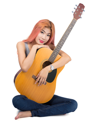 Happy girl hugging a guitar on white background.