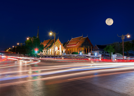 Moon on night sky over Wat Phrathat Chang Kham Worawihan in twilight scene with light trails from long exposure.