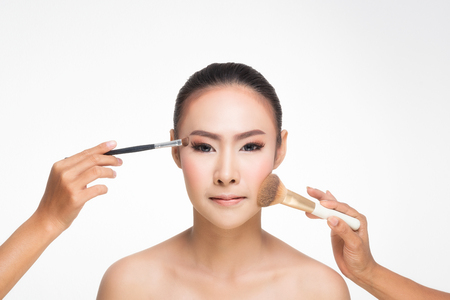 Close up portrait of a girl woman applying cosmetic tonal foundation on her face using makeup brush and hand. Stockfoto