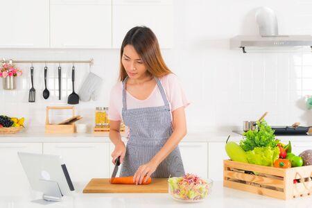 Hermosa mujer asiática, cabello largo, vestida con una camiseta rosa y un delantal a rayas de pie, cortando zanahorias en la mesa en la moderna cocina blanca y viendo un videoclip de cocina con tableta. Foto de archivo