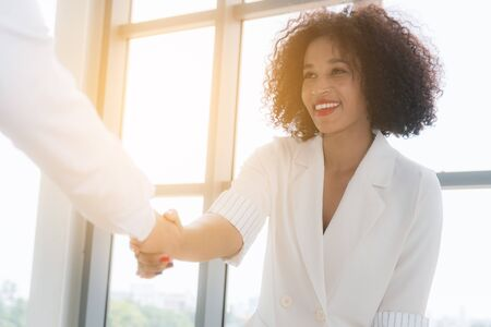 African American lady business woman shaking hand as they close a deal or partnership focus to smiling on sunlight background at office. Banco de Imagens