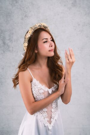 Vintage style portrait beautiful woman wearing a white dress, flower crown on gray soft blurred background.