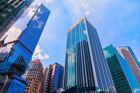 Ansicht von unten auf Hochhaus und moderne Wolkenkratzer im Geschäftsviertel gegen blauen Himmel.