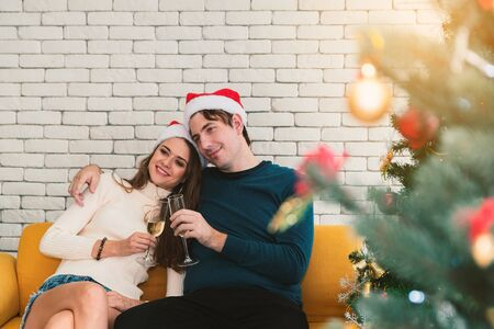 European couples, caucasian man wearing blue sweater and woman wearing white sweater, wearing christmas hat sitting drinking white wine in christmas season at sofa.