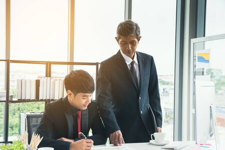 Senior businessman explaining business matters to the junior businessman. Adult manager teaches, suggests working for new businessmen at the desk.