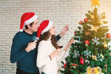 Celebration of the Christmas of couples. Young man are embracing their girlfriends, holding a glass of wine and enjoying standing beside the Christmas tree in the room.