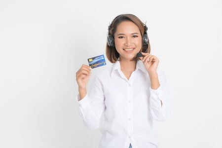 Friendly female helpline operator or call center showing blank credit card, headset holding her arms crossed isolated on white background. Фото со стока