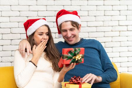 European couples, caucasian man wearing blue sweater and woman wearing white sweater, wearing christmas hat giving a Christmas present to his girlfriend in christmas season at sofa.