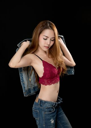 Asian girl in jeans shows red lingerie on black background