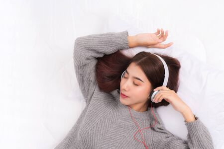 Young beautiful woman wearing a gray sweater is lying and listening to music wearing white music headphones on the bed. She is relaxing and down with eyes closed at happiness. 版權商用圖片