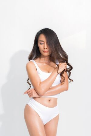 Beautiful asian woman black hair and long hair wearing a white swimsuit in posting standing summer fashion on isolated white background and shadow.