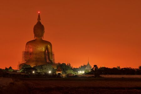 Back view, Big golden buddha in sunrise or sunset time. at Wat Muang in Ang Thong, Thailand.