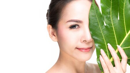 Close-up studio shot, Beautiful young woman with clean fresh skin holding green leaves. Proposing a product. Gestures for advertisement isolated on white background.