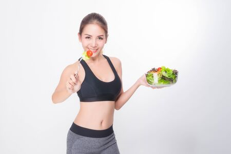Asian woman portrait with perfect skin smiling face happy wearing black-gray exercise clothing holding a bowl of vegetable salad and fork on white background. Concept healthy. Stock Photo