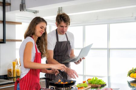 Romantic couple is cooking on kitchen. Healthy lifestyle concept. Handsome man and beautiful woman are having fun together while making steak and salad.