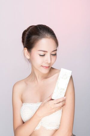 Beautiful young woman with clean fresh skin, Hair sleek, Proposing and holding a product mockup, gestures for advertisement on pink background, Front view, with copy space.