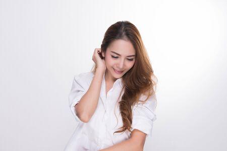 Retrato de mujer asiática con una piel perfecta y con una camisa blanca de perfil aislado sobre fondo gris.