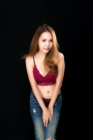 Beautiful asian woman long brown hair fashion sexy portrait wears red underwear with jeans on black background.