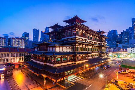 Buddha-Zahn-Relikt-Tempel in Chinatown in Singapur, mit Singapurs Geschäftsviertel im Hintergrund im schönen Morgenhimmel. Editorial