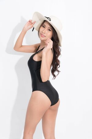 Beautiful asian girl wearing black swimming suit dress, wearing a white hat in a standing position looked up at the top in a summer fashion on isolated white background. Reklamní fotografie