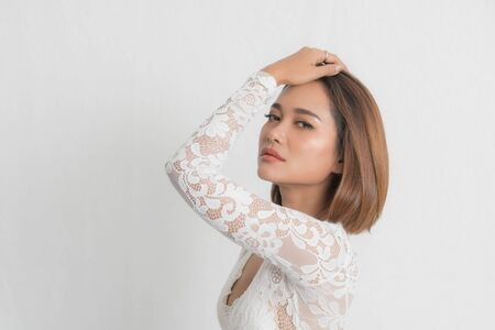 Beautiful portrait asian woman brown short bob wearing a white lace bodysuit on isolated white background. In close-up view