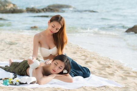 Asian woman are happy and relaxed massage at a spa on the beach in the evening. 免版税图像