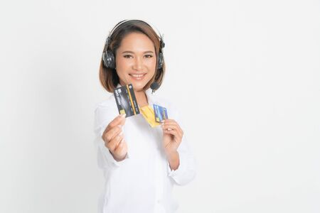 Friendly female helpline operator or call center showing blank credit card, headset holding her arms crossed isolated on white background. Banque d'images - 144120440