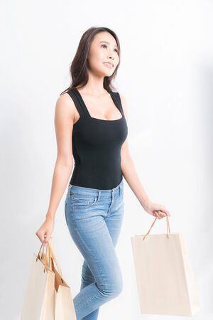 Happy beautiful asian woman black long-haired woman wearing a black shirt, blue jeans carrying shopping bags on isolated gray background, Shopping summer sale concept.
