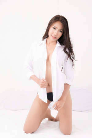 Sexy lifestyle portrait of beautiful alluring young woman brown long haired sexy wear a white shirt no bra. in white bedroom. Concept fashion sexy in bed. Studio shot.