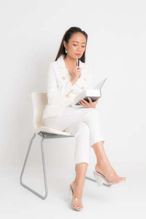 Fashion style catalog clothing for business woman black long hair natural make up wear white suit sitting on white chair, holding book and pens at studio shoot on white background.