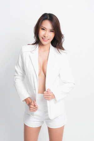 Fashion style body length studio portrait. Woman in white suit with loose dry hair and makeup posing on a white background.