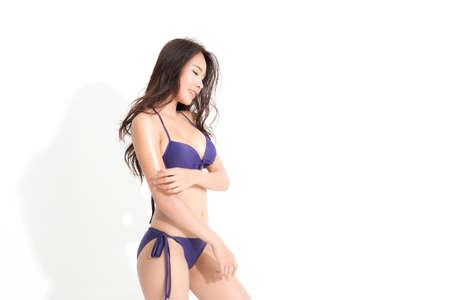 Beautiful asian woman with long brown hair wearing purple bikini dress in a summer fashion posing studio shot isolated on white background and shadow. Zdjęcie Seryjne