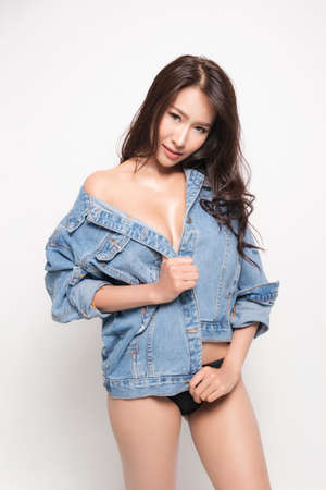 Beautiful asian woman with long brown hair wearing blue jeans jacket with no bra is sexy fashion position studio shot isolated on white background.