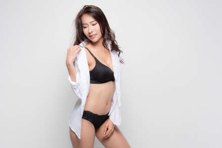 Beautiful asian woman with long brown hair wearing white shirt and black bra, sexy fashion position studio shot isolated on gray background.