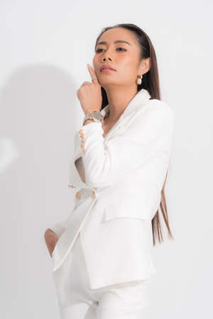 Fashion style catalog clothing for business woman black long hair natural make up wear white suit costume perfect body shape suit at studio shoot on white background and shadow.