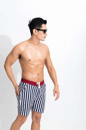 Young muscular guy in striped beach shorts sunbathing wear sunglasses at studio shot isolated on white background. Fashion summer concept. Zdjęcie Seryjne