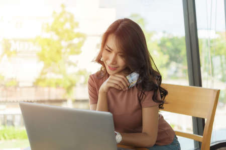 Beautiful woman wearing a brown shirt sitting and smiling face happy sitting by a large window, She is shopping online with laptop and holding credit card. Zdjęcie Seryjne