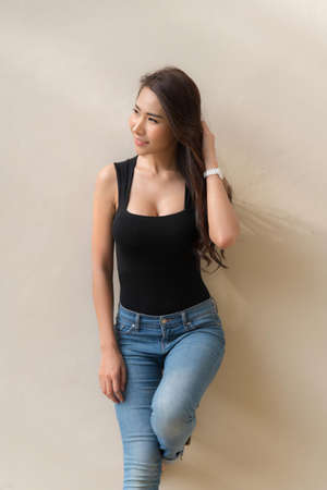 Beautiful woman long brown hair smiling with wearing a black t-shirt and jeans standing posting on beige color wall. Zdjęcie Seryjne