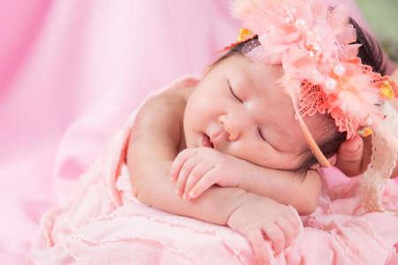 Portrait of a one month old sleeping, newborn baby girl. She is wearing a flower crown and sleeping on a pink blanket. Concept portrait studio fashion newborn. Zdjęcie Seryjne