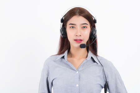 Portrait of happy smiling female customer support phone operator short hair, wearing a white shirt with headset standing one side holding the earphone isolated on white background.