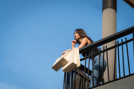 Beautiful woman is leaning on the railing of the balcony looking into the distance standing with a shopping bag on blue sky background. Worm's-eye view. Zdjęcie Seryjne