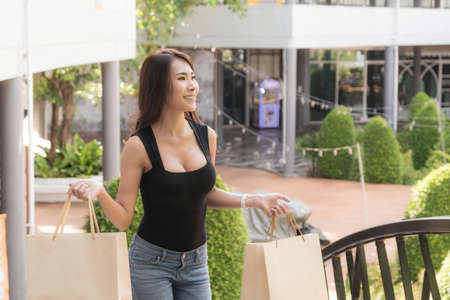 Beautiful woman wearing a black shirt and jeans perfect body shape, is walking up the stairs with carrying shopping bag at outdoor shopping mall in day time.