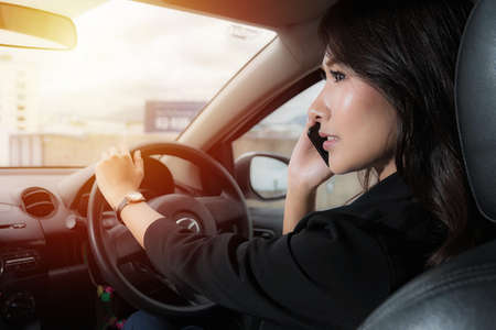 Beautiful asian woman wear black suit work clothes talking on a mobile phone at car in evening time on sunlight background.